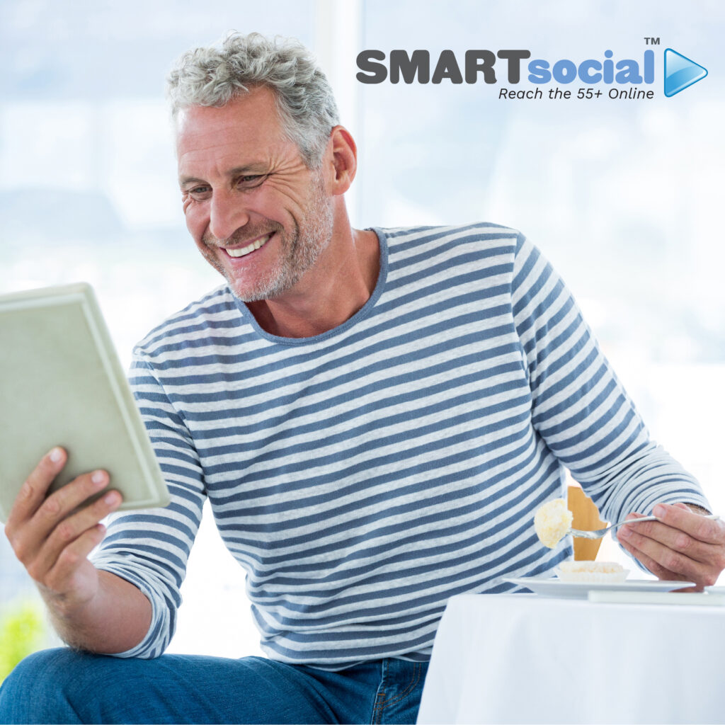 55 YEAR OLD MAN EATING WHILE READING TABLET AND SMILING