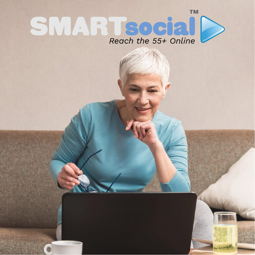MATURE WOMAN ON SOFA WITH COMPUTER WITH SMARTSOCIAL LOGO